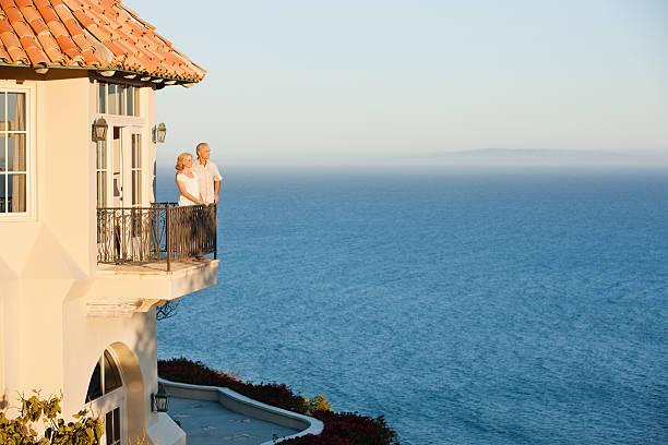 Couple de senior sur le balcon de sa maison en bord de mer